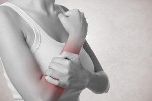 Frau mit Schmerzen im Unterarm